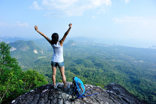 Woman on the top of a mountain with her airms raised in success