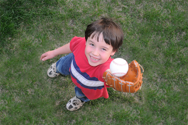 little boy in a red striped shirt catching a baseball in his mitt from the air