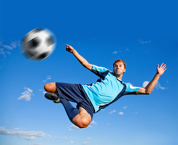 male soccer player doing a bicycle kick in midair