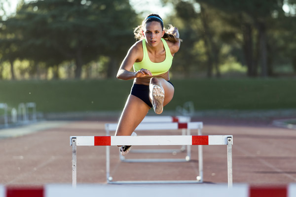 woman doing hurdles with right leg in the air