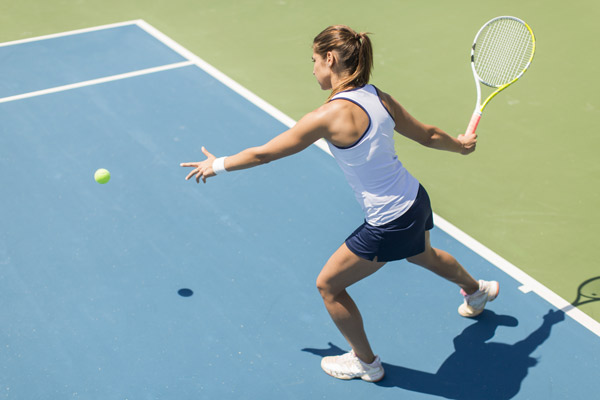 woman playing tennis on the courts ready to swing and hit the ball
